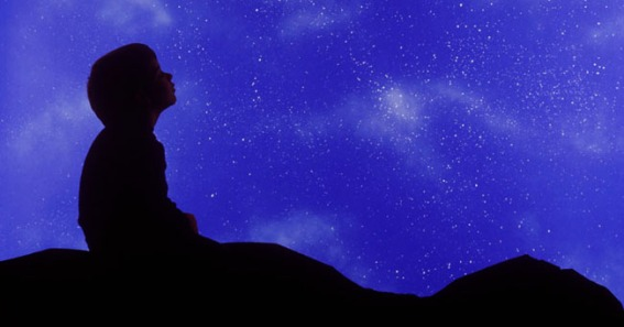 Square image of a small child in profile looking up at a star filled night sky.